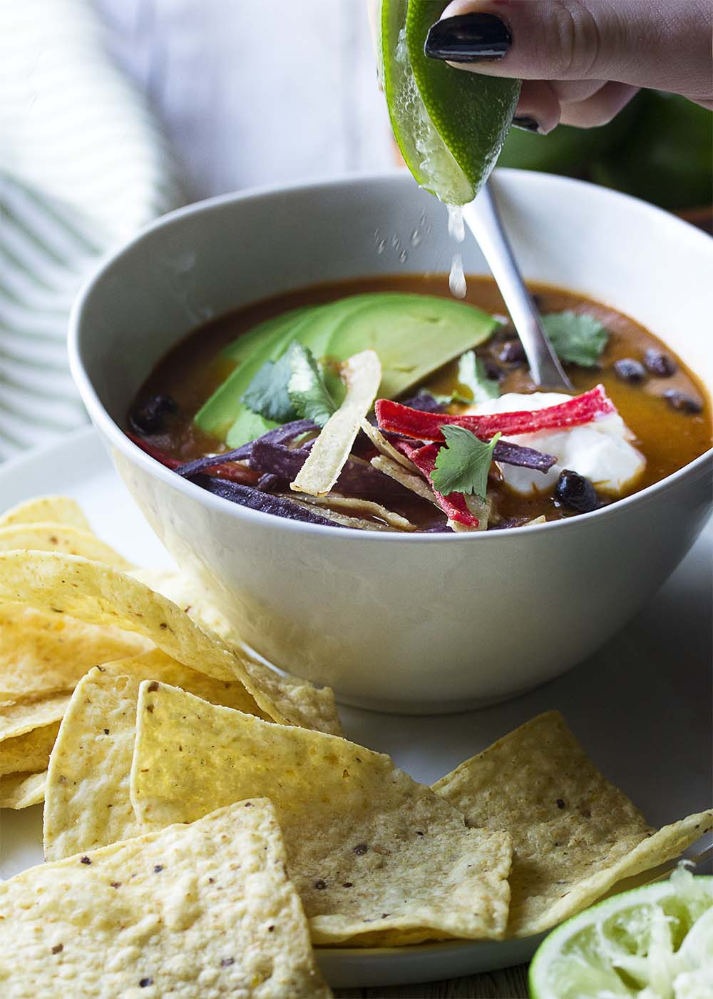 A hand squeezing a lime into a bowl of vegetarian tortilla soup. Soup loaded with toppings and tortilla chips.