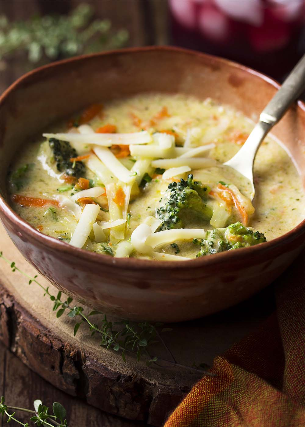A bowl of broccoli soup topped with shredded cheese. A spoon in the bowl.