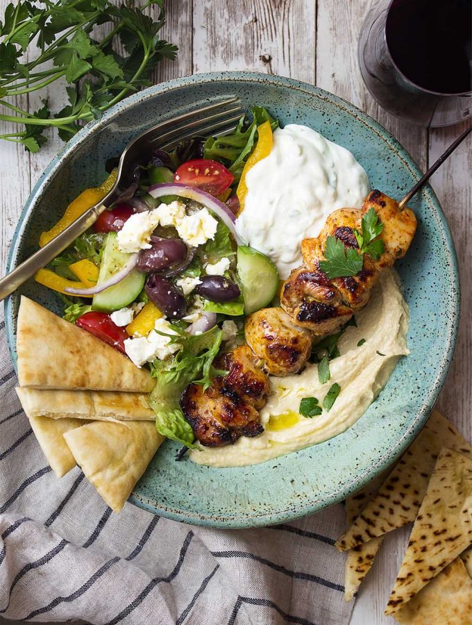 Enjoy Greek and Mediterranean flavors in my hummus bowl topped with marinated and grilled chicken souvlaki skewers, a green salad, tzatziki sauce, and crisp pita bread triangles. | justalittlebitofbacon.com #greekfood #mediterraneanfood #hummus #chickensouvlaki #greekdinners #grilledrecipes