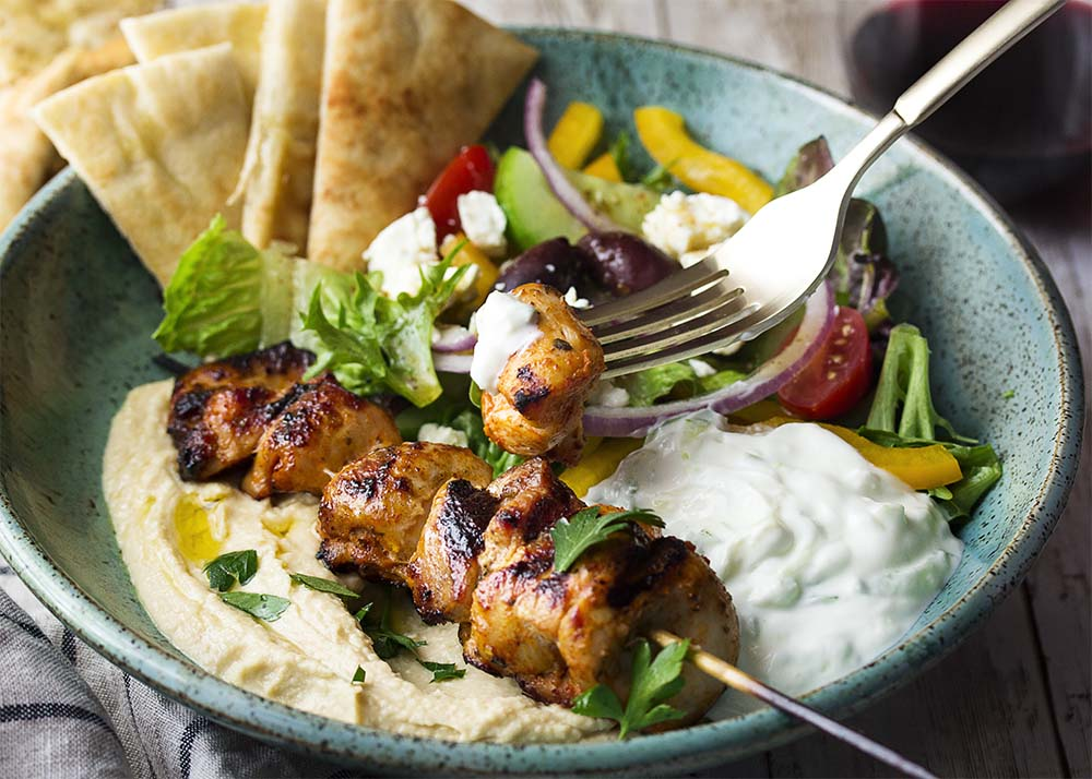 A fork holding up a piece of chicken souvlaki topped with tzatziki in a dinner bowl. Pita, Greek salad, and hummus also in the bowl.
