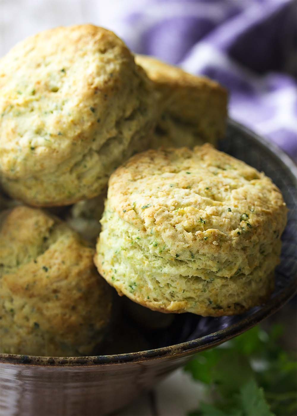 A bowl full of fluffy and tender buttermilk biscuits, each fleckled with chopped herbs.