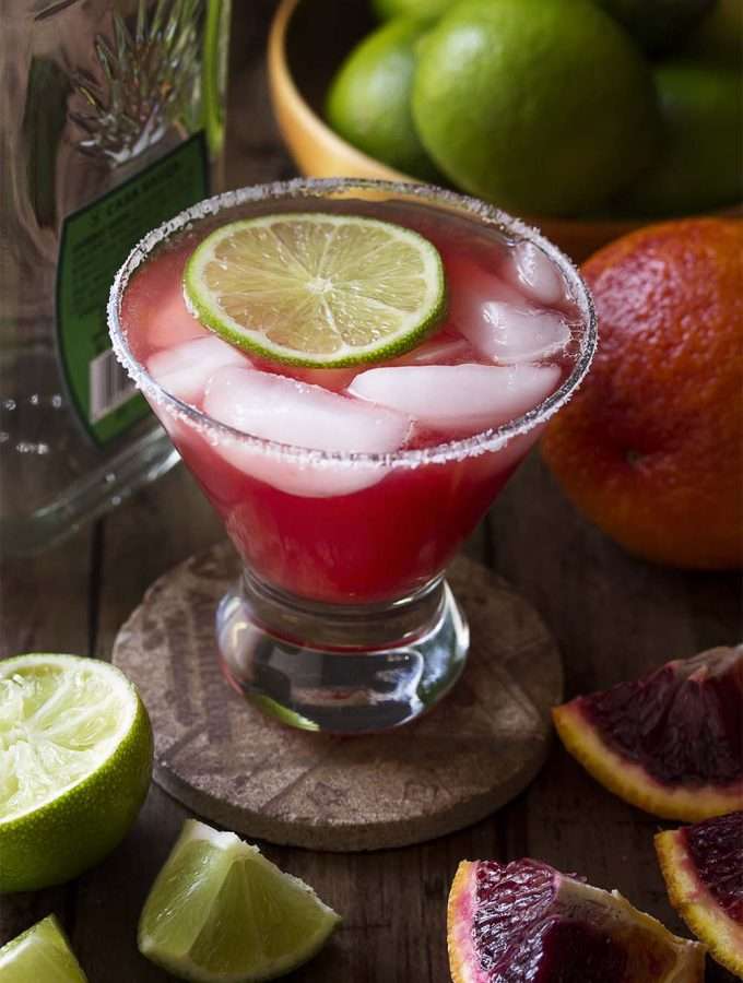 Try something a little different and learn how to make a blood orange margarita! Grab your tequila and mix up one or make a pitcher for a crowd. Either way you'll love this easy and delicious homemade cocktail. | justalittlebitofbacon.com #cocktails #drinkrecipes #margaritas #bloodoranges #pitcherdrinks