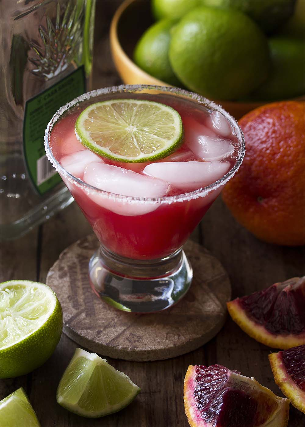 A blood orange margarita in a glass with a slice of lime. Limes and blood oranges scattered around.