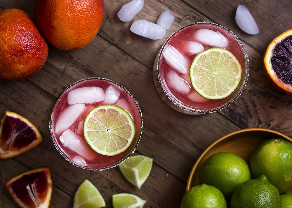 Top view of two blood orange margaritas on the rock each with a slice of lime on top.