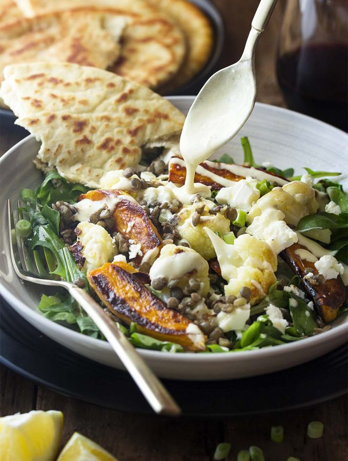 Roasted cauliflower and sweet potato combine with tender French green lentils and peppery arugula in this delicious warm salad all topped with a creamy yogurt and tahini dressing. Perfect for a healthy Mediterranean vegetarian dinner! | justalittlebitofbacon.com #saladrecipes #mediterraneanfood #lentilrecipes #frenchlentils #cauliflower #sweetpotatoes