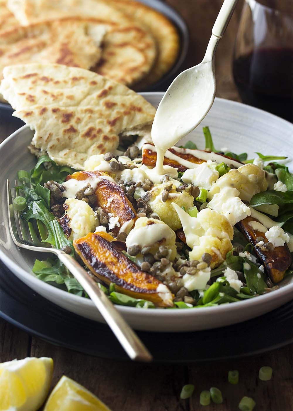 A spoon drizzling creamy yogurt tahini dressing over a bowl filled with sweet potato, cauliflower, and lentil salad.