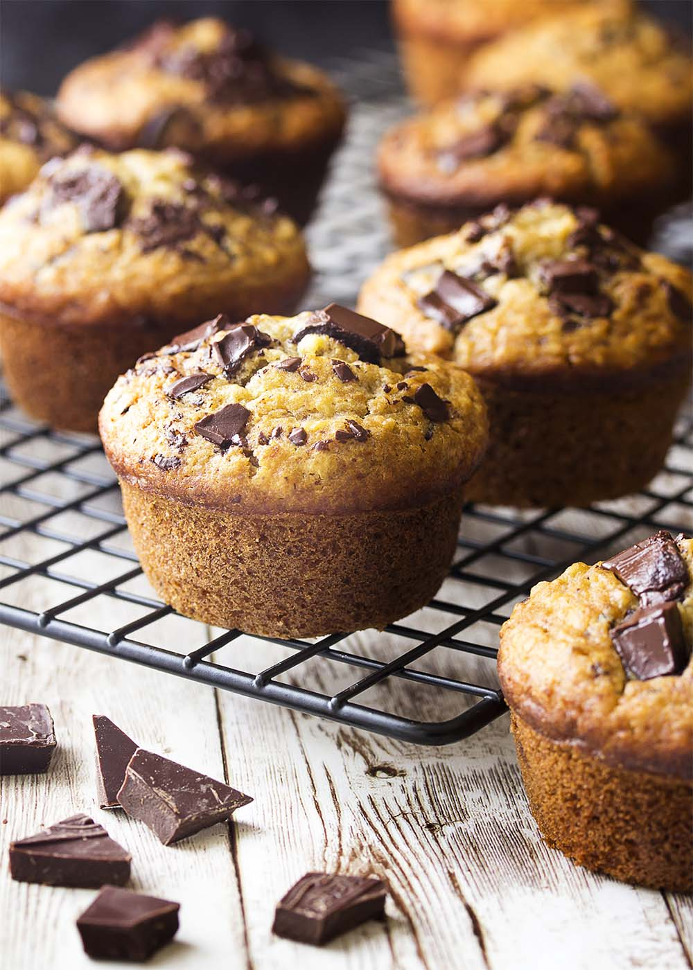 Serveral chocolate banana oat muffins on a cooling rack. Each golden brown with a domed top.