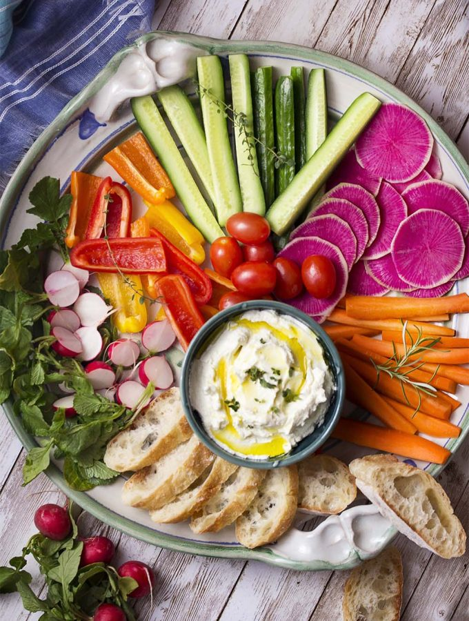 Dip your favorite crudites and crackers into my easy garlic goat cheese spread! This cold herbed appetizer can be made in minutes and use just a few ingredients. | justalittlebitofbacon.com #appetizerrecipes #diprecipes #goatcheese #appetizers #dips #spreads