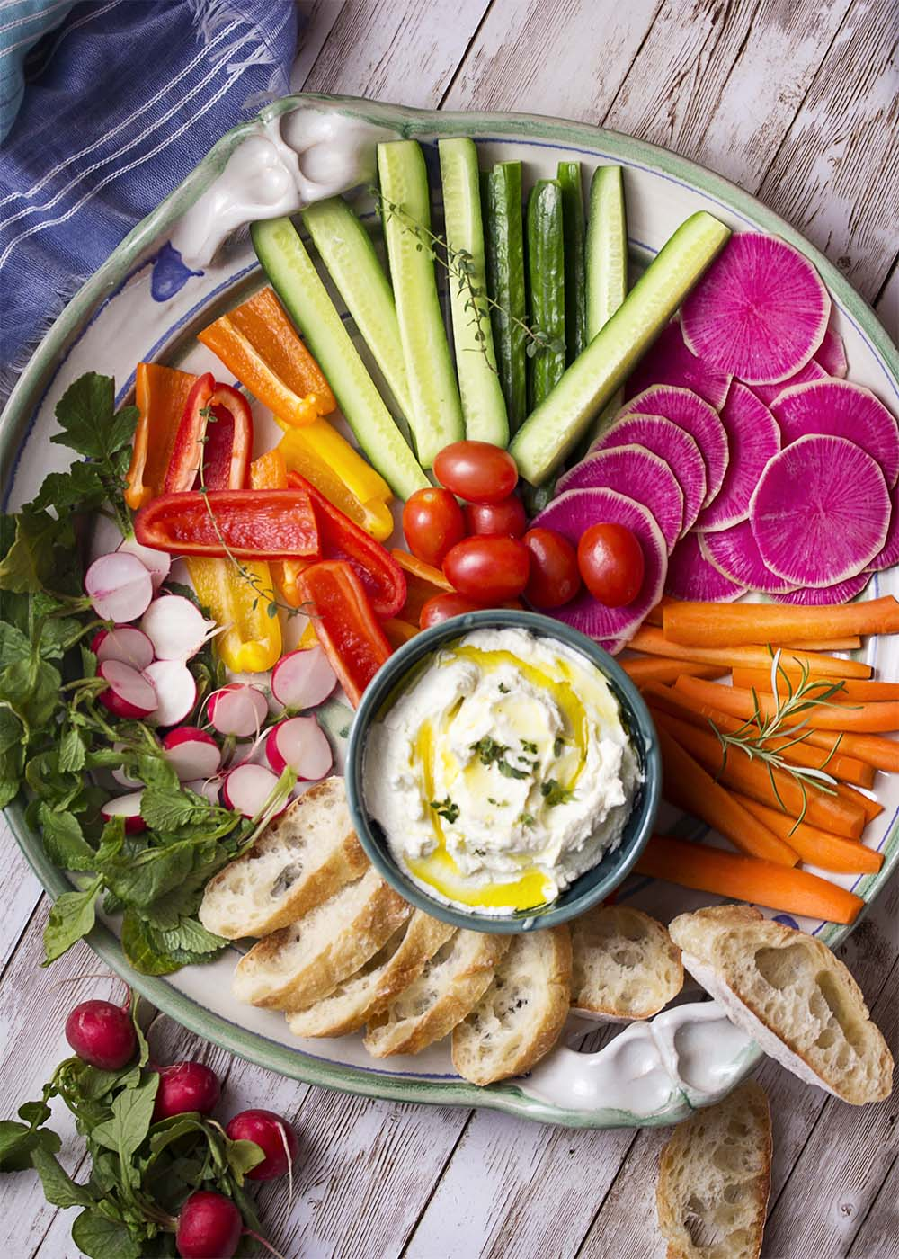 Top view of a table with a large platter filled with colorful cut vegetables and sliced bread. A bowl of whipped goat cheese in the platter.