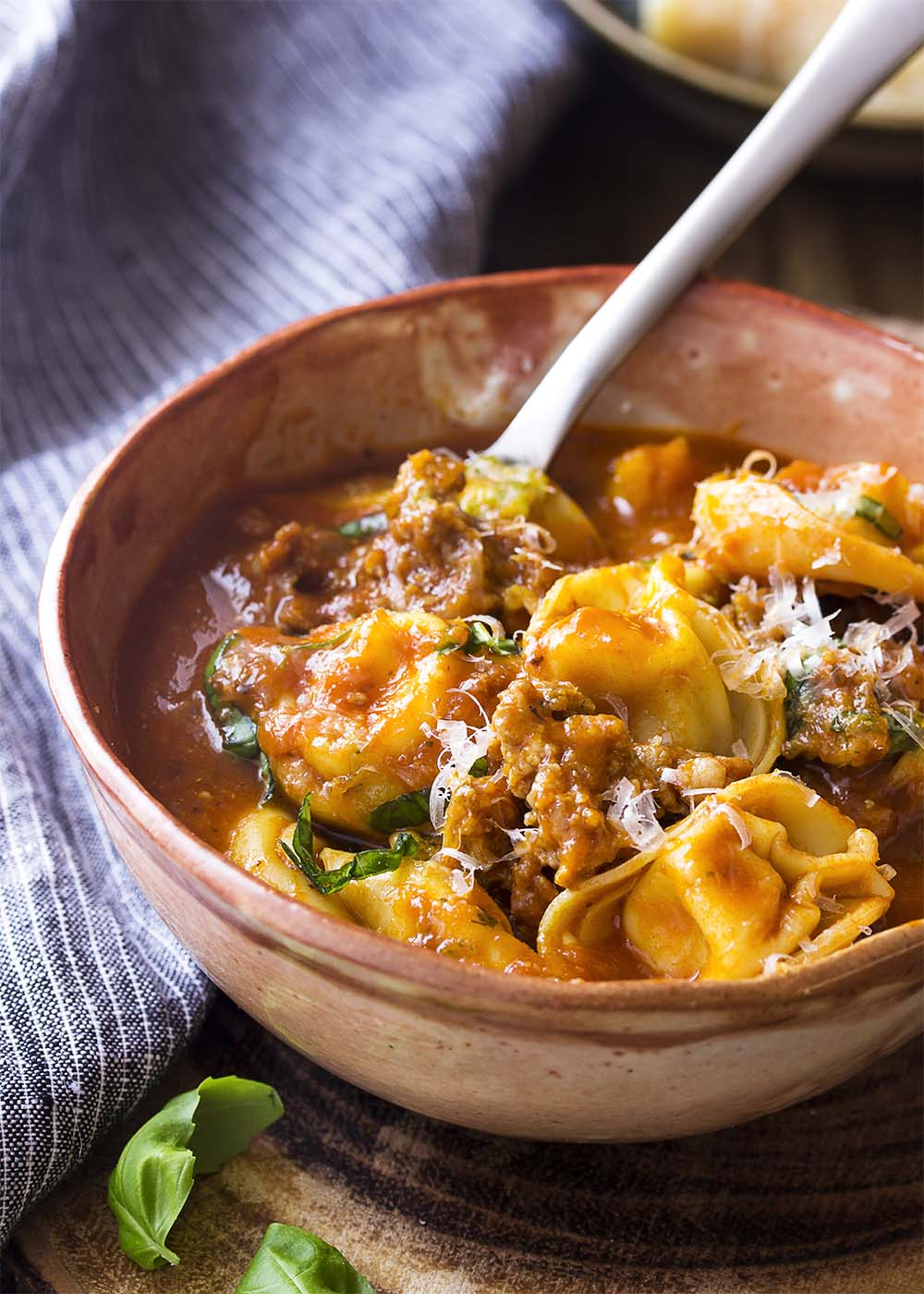 Italian sausage tortellini soup in a brown bowl with a spoon.