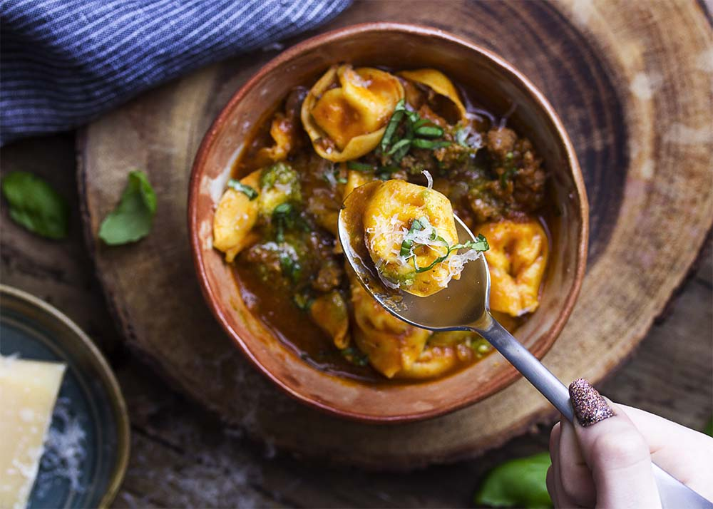A hand holding up spoon with a tortellini over a bowl of soup.