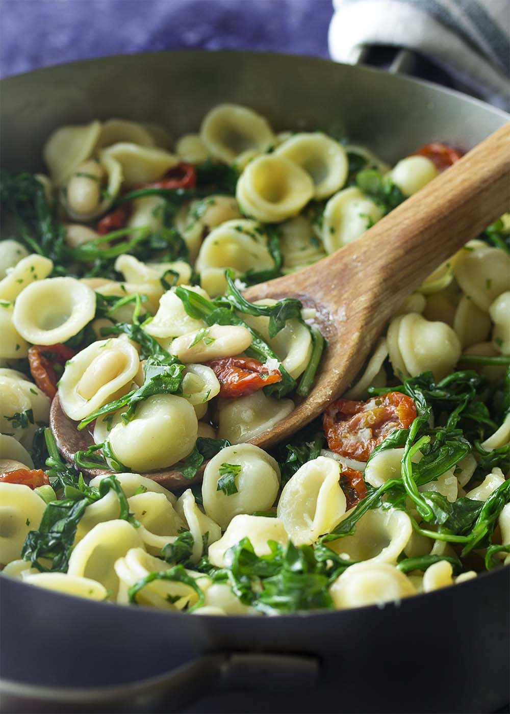 Pasta with white beans, arugula, and tomatoes in a skillet. A wood serving spoon scooping up a portion.