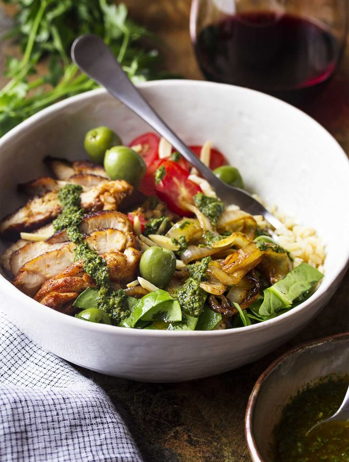 Juicy grilled thighs and whole grains make up the base of this healthy Moroccan inspired chicken rice bowl which is tossed with greens and tomatoes, then drizzled with a spicy cilantro chermoula sauce. | justalittlebitofbacon.com #saladrecipes #chickenrecipes #grilledchicken #chickenandrice #dinnerrecipes #chicken
