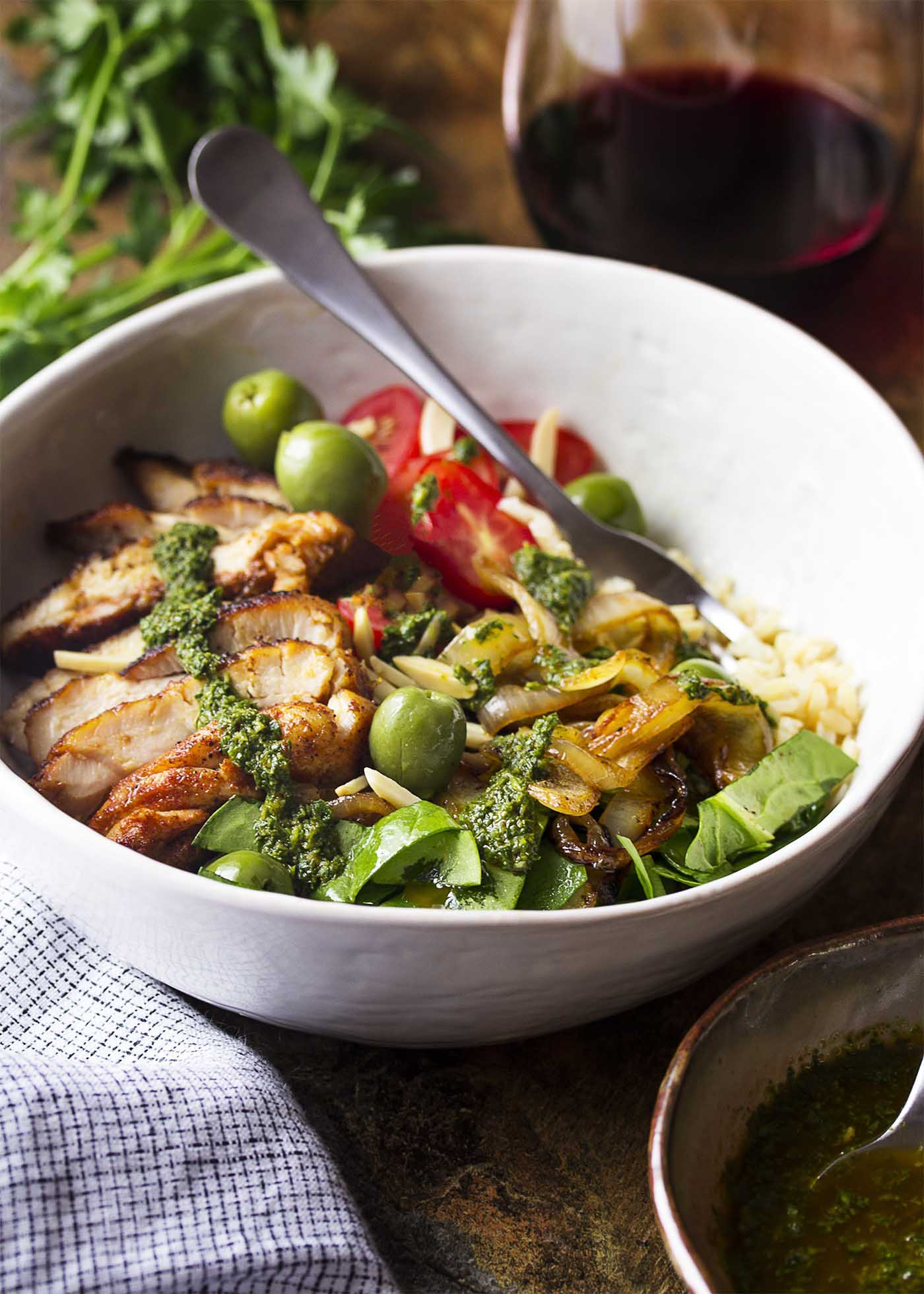 Grilled sliced chicken over rice with onions, greens, tomatoes and olives all in a white bowl.