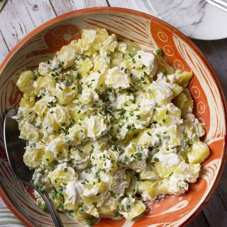 My creamy potato salad with peas and horseradish is tossed with sour cream and mayonnaise. Easy, homemade, and simple! Top with chives for extra zip. | justalittlebitofbacon.com #saladrecipes #potatosalad #potatorecipes #summerrecipes #bbqrecipes #summer #potatoes