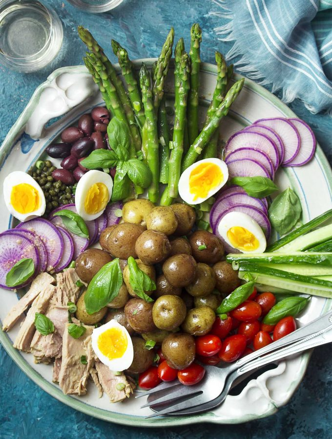 Canned tuna packed in a jar of olive oil and fresh asparagus are featured in my spring nicoise salad! Set it up on a large platter for the best presentation and enjoy all the crisp vegetables, soft boiled eggs, and creamy potatoes all drizzled with a simple lemon dressing. | justalittlebitofbacon.com #saladrecipes #frenchrecipes #springrecipes #spring #salad #frenchfood #asparagus
