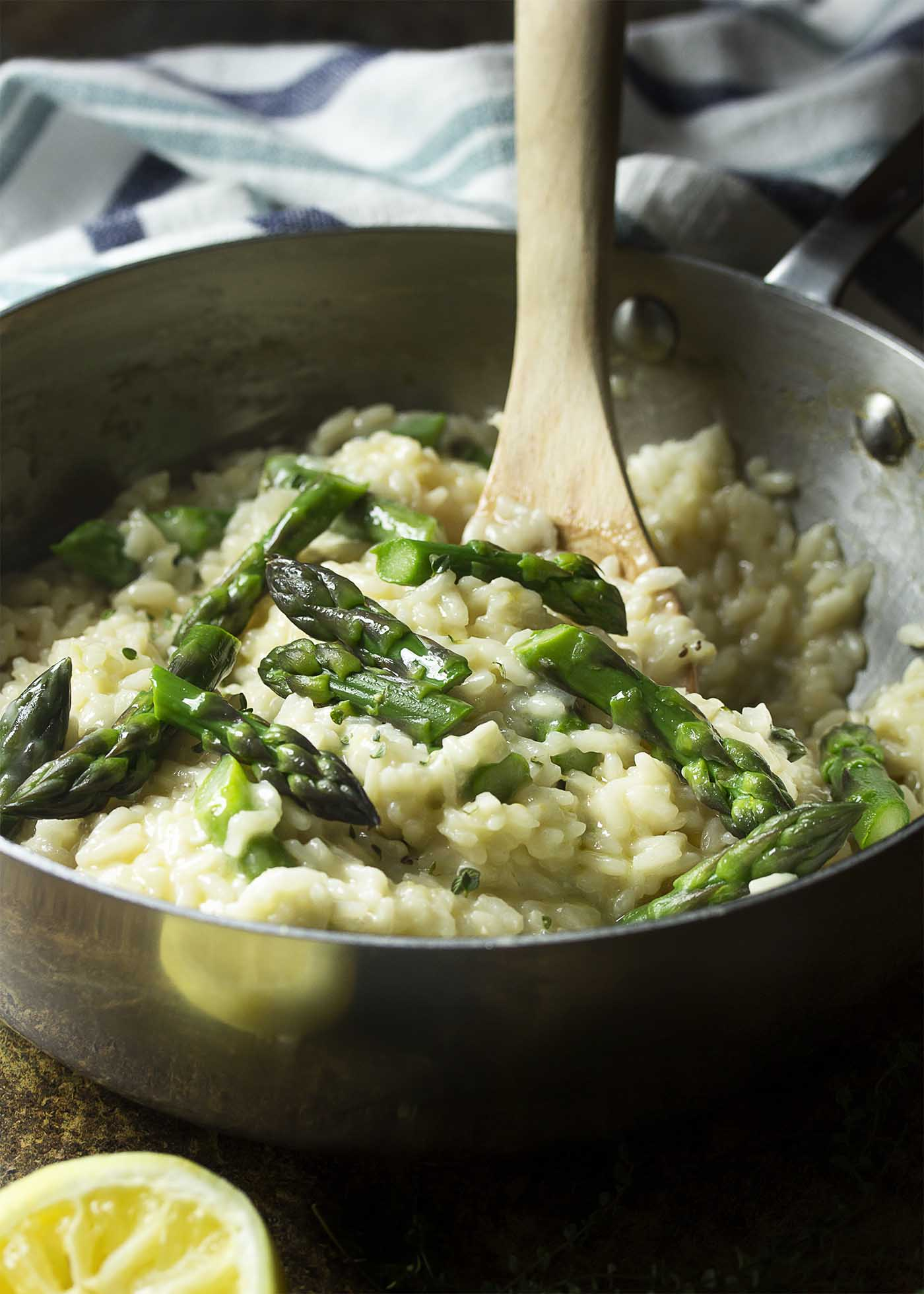 Wooden spoon stirring a finished saucepan of creamy risotto and asparagus.