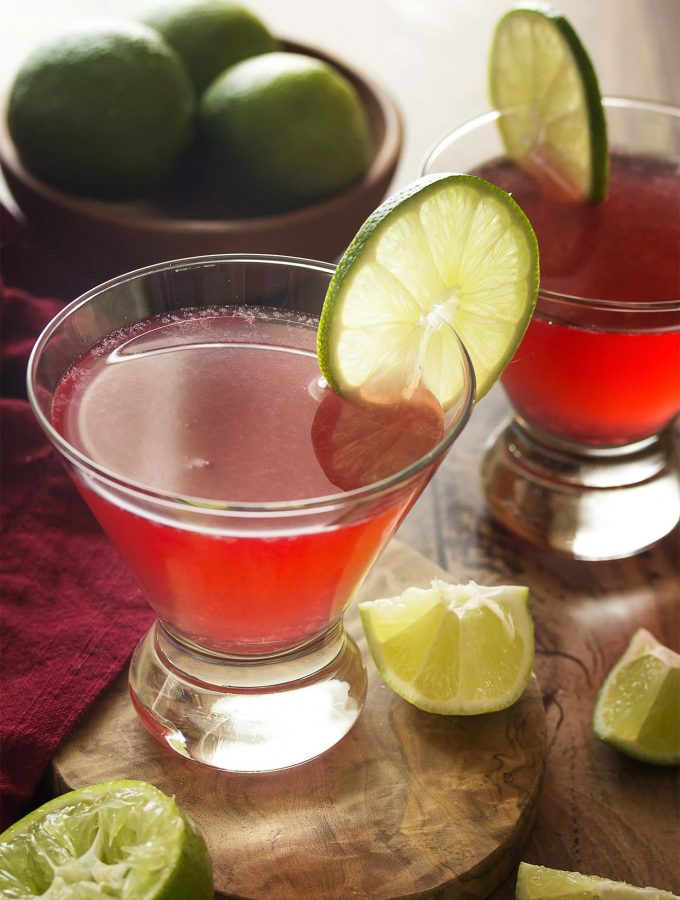 Learn how to make a cosmopolitan martini, a classic drink which is both easy and delicious! Four ingredients (including cranberry juice and vodka) are all you need to be sipping this fun pink cocktail right now. | justalittlebitofbacon.com #cocktailrecipes #drinkrecipes #cosmopolitan #vodkacocktails #martinis #cranberryjuice