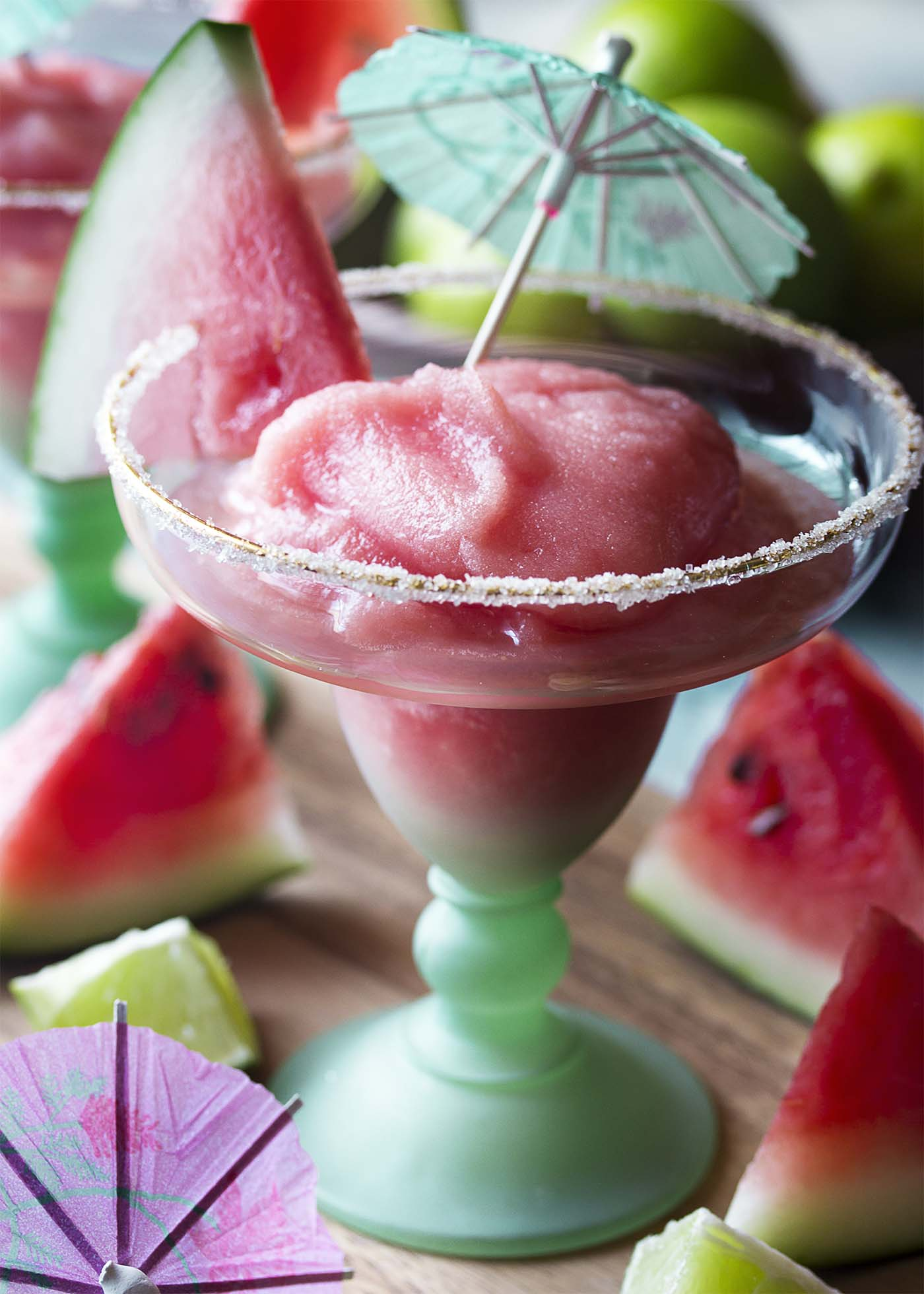 Close up of a thick frozen watermelon margarita in a teal stemmed glass with sugar.