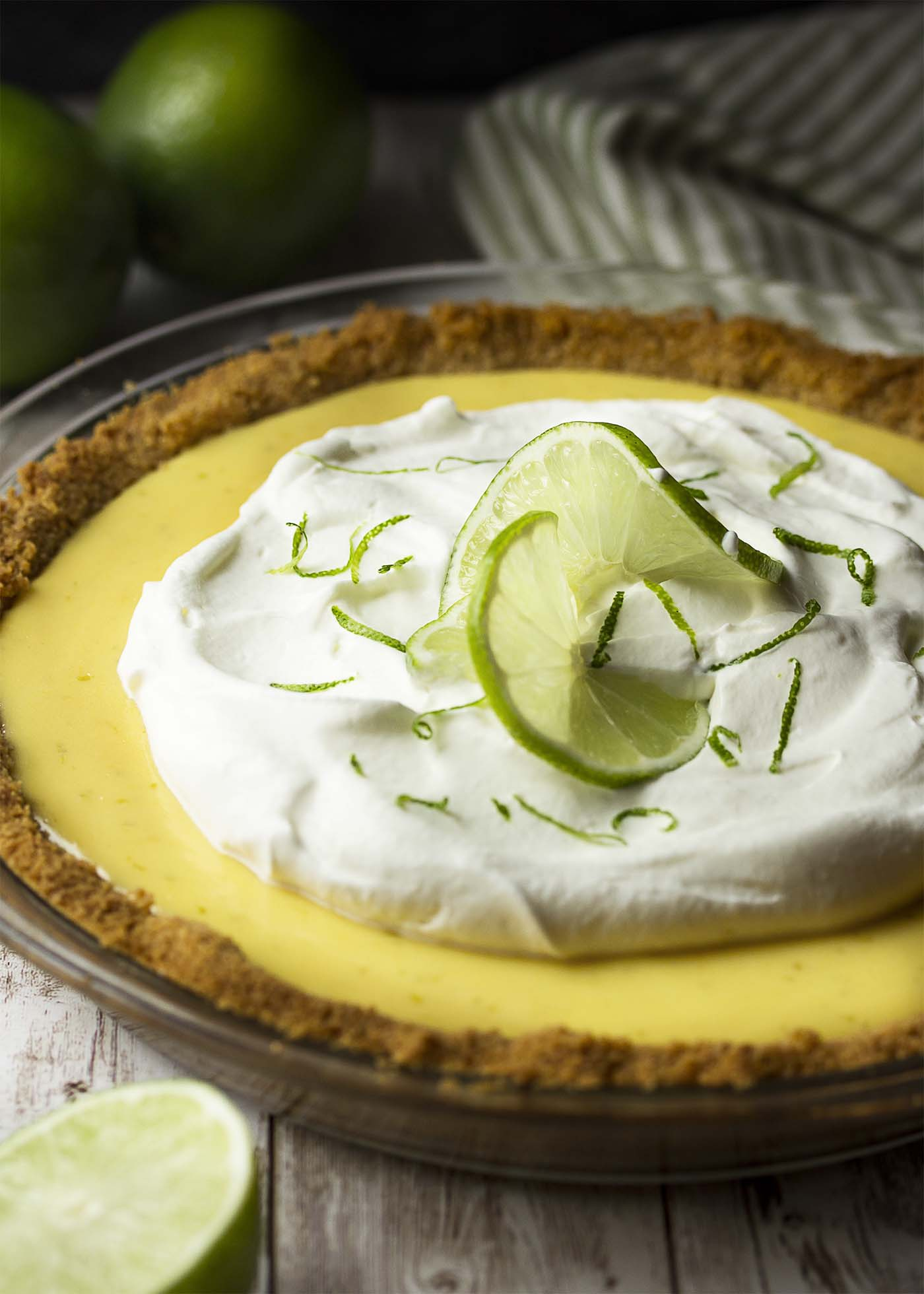 Whole pie with graham cracker crust, topped with whippd cream and lime zest.