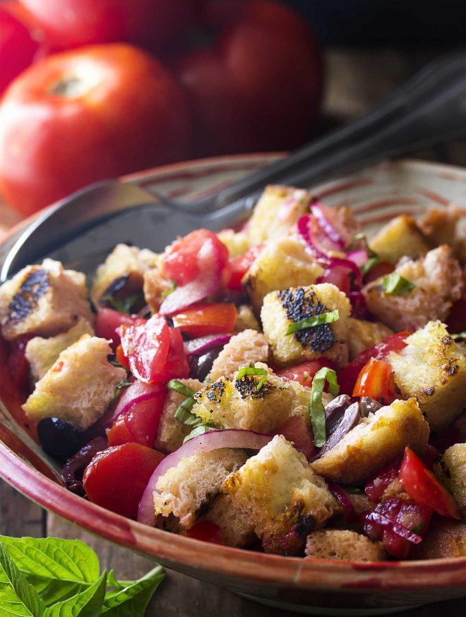 Make the most of flavorful summer tomatoes with this amazing Italian panzanella salad! Perfectly ripe tomatoes, smokey grilled bread, plenty of basil, and light and tangy vinaigrette all come together for a side dish you'll love all season long. | justalittlebitofbacon.com #italianfood #summerrecipes #saladrecipes #tomatoes #salads #grillingrecipes #veganfood