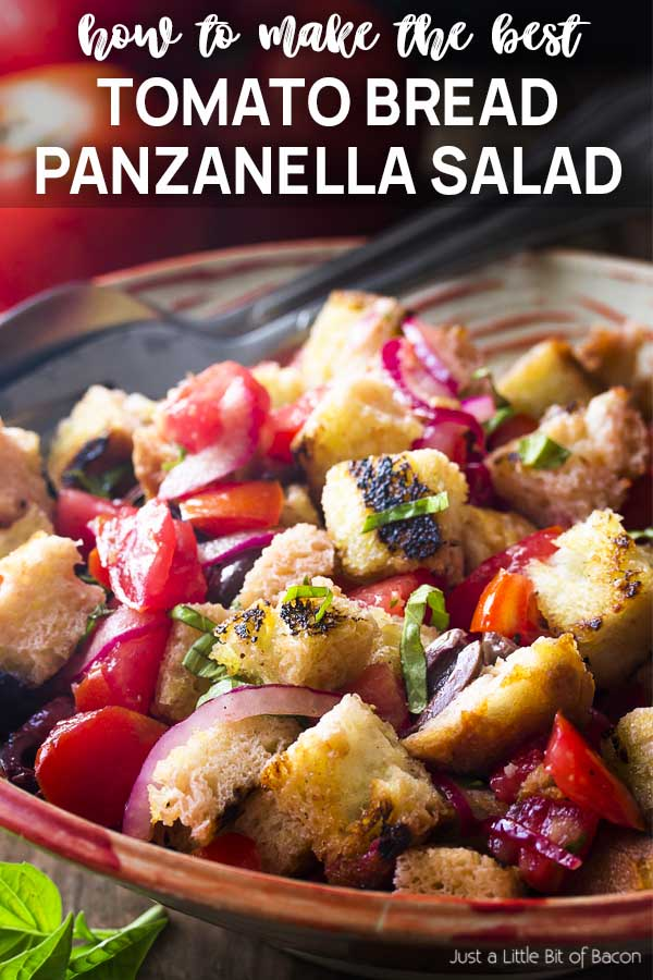 Serving bowl salad with serving fork and spoon and text overlay - Tomato Bread Panzanella Salad.