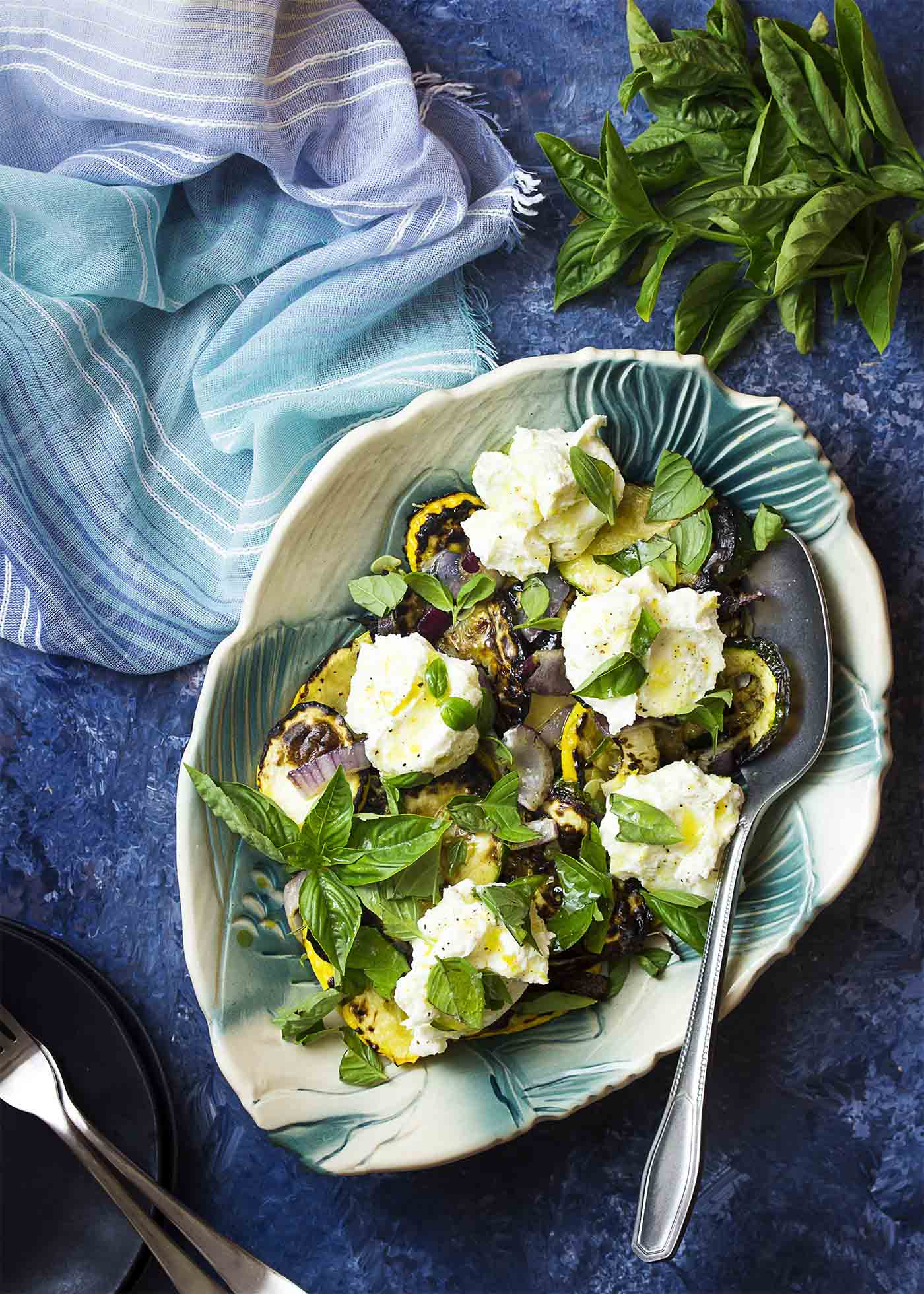 Serving dish of grilled zucchini salad with lemon ricotta and fresh basil over the top.