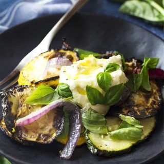 For an easy side make grilled zucchini salad with lemon ricotta! This Mediterrean recipe is delicious warm or room temperature and is wonderful with a mix of green and yellow summer squash. | justalittlebitofbacon.com #italianfood #summerrecipes #saladrecipes #salads #grillingrecipes #zucchini #ricotta
