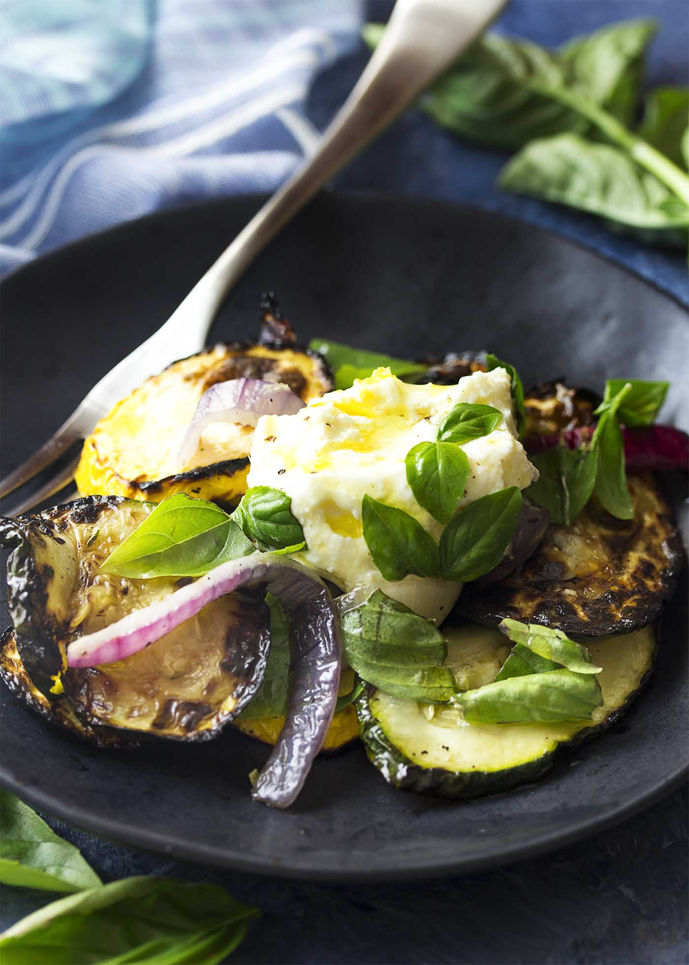 Black plate of grilled summer squash salad with a spoon of lemon ricotta on top.