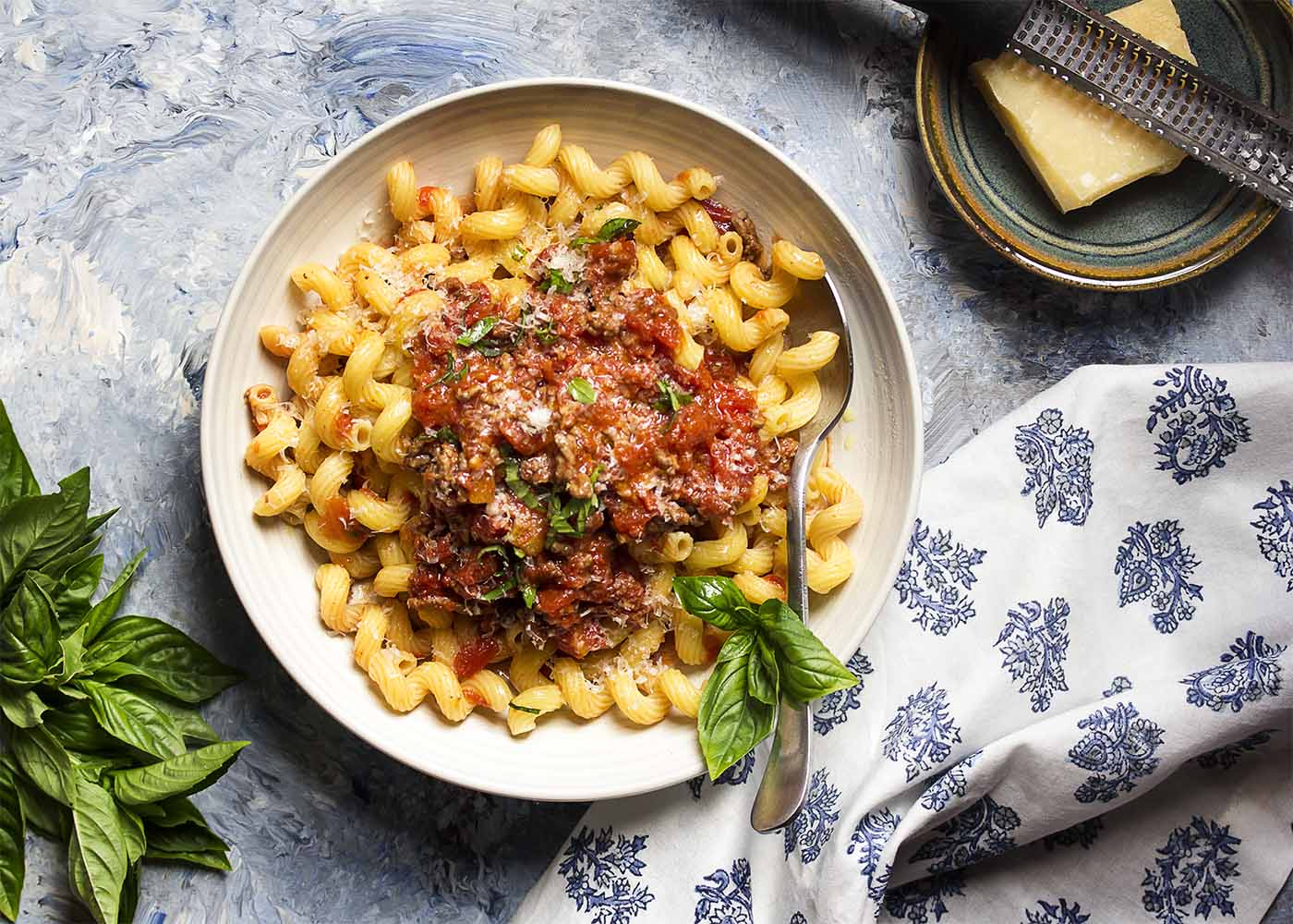 Top view of a bowl of pasta toppped with meat sauce and sliced basil.