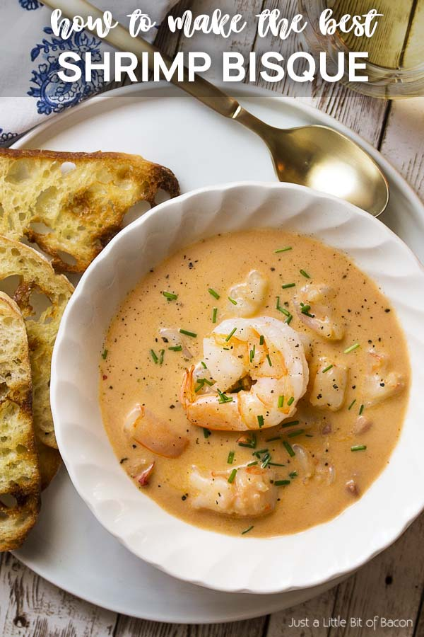 Soup in a white bowl on a plate with text overlay - Shrimp Bisque.