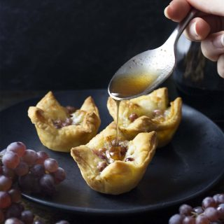Puff pastry brie bites filled with grapes and honey are a fun and easy party appetizer! These baked mini tarts can be prepped ahead making them perfect for Thanksgiving, Christmas, coctail parties, and other holidays. | justalittlebitofbacon.com #partyfood #appetizers #thanksgiving #christmas #puffpastry