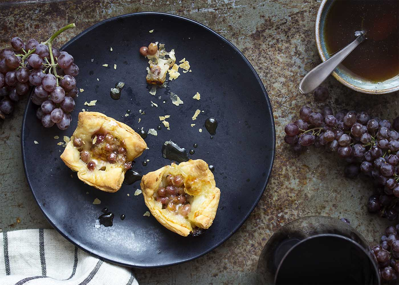 Top view of a black plate with two grape and brie tarts each topped with honey.