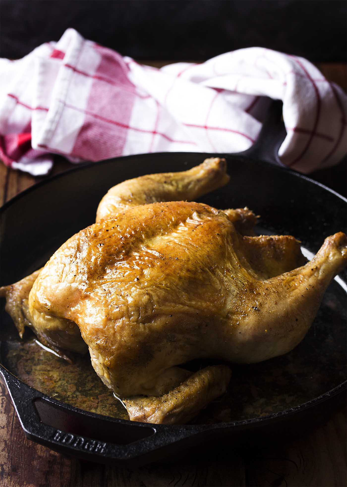 Golden brown roast chicken in a cast iron pan.