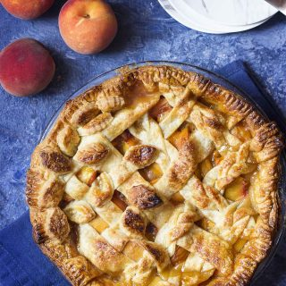 My homemade peach pie is an old fashioned treat filled with fresh peaches, brown sugar, and bourbon for the best flavor! The juicy filling is topped with a lattice crust for a dessert which is both delicious and beautiful. Perfect for holidays like Thanksgiving and Christmas! | justalittlebitofbacon.com #pierecipes #dessertrecipes #thanksgiving #holidays #summerrecipes #peaches