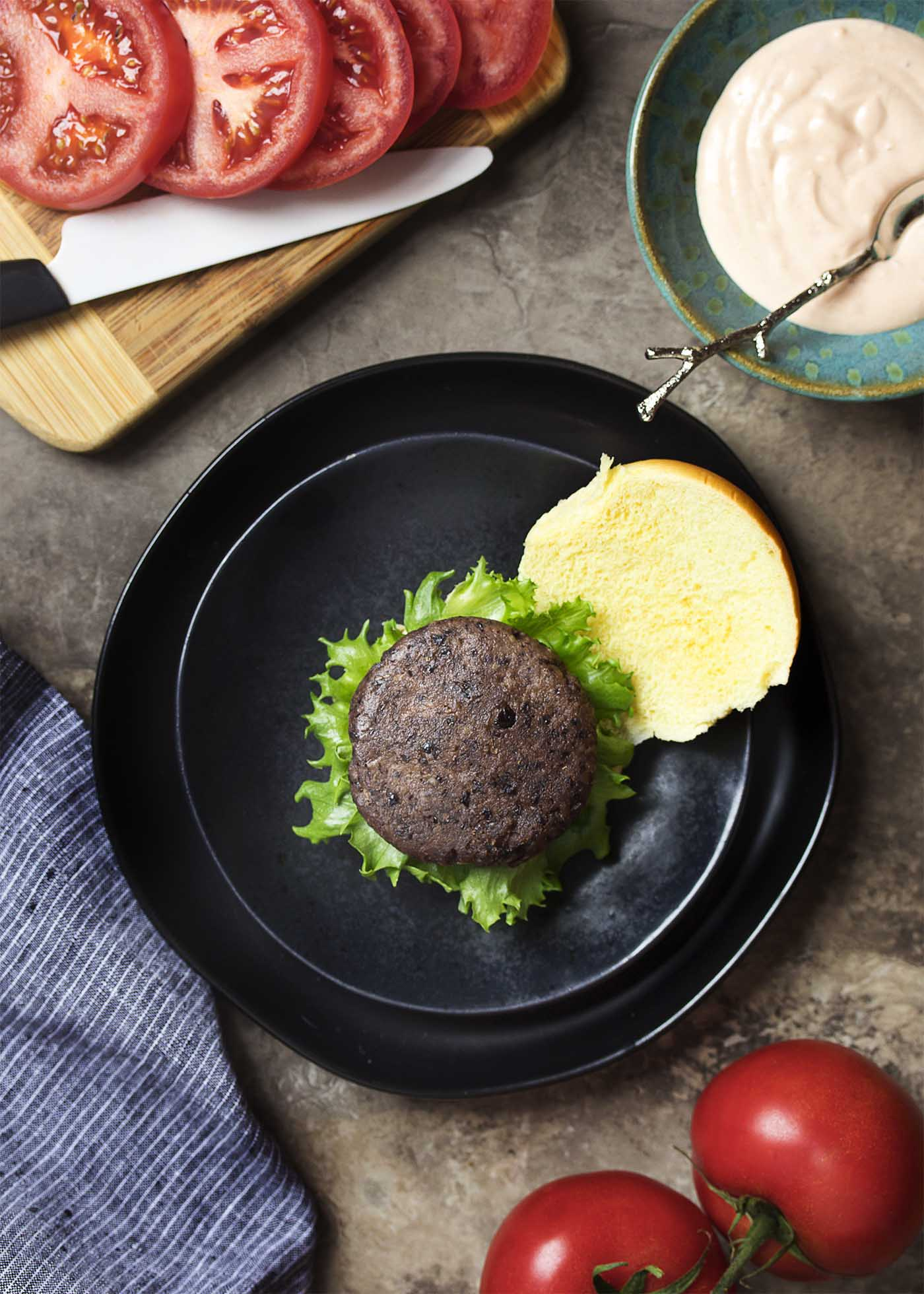 Top view of a black bean burger on a bun with lettuce ready for a slice of tomato and sauce.