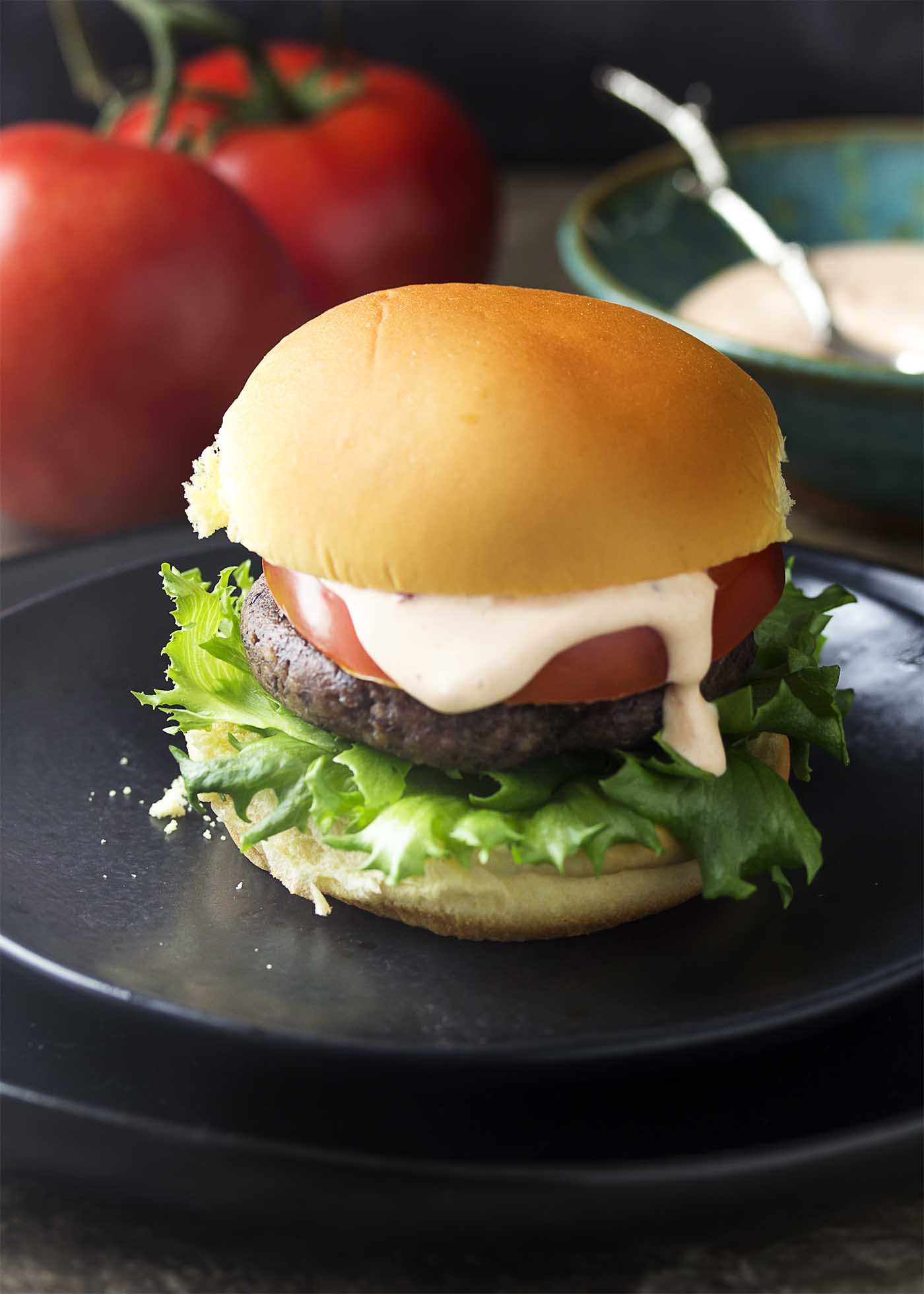 Close up of a bean burger on a black plate. Burger on a bun with lettuce, tomato, and sauce.