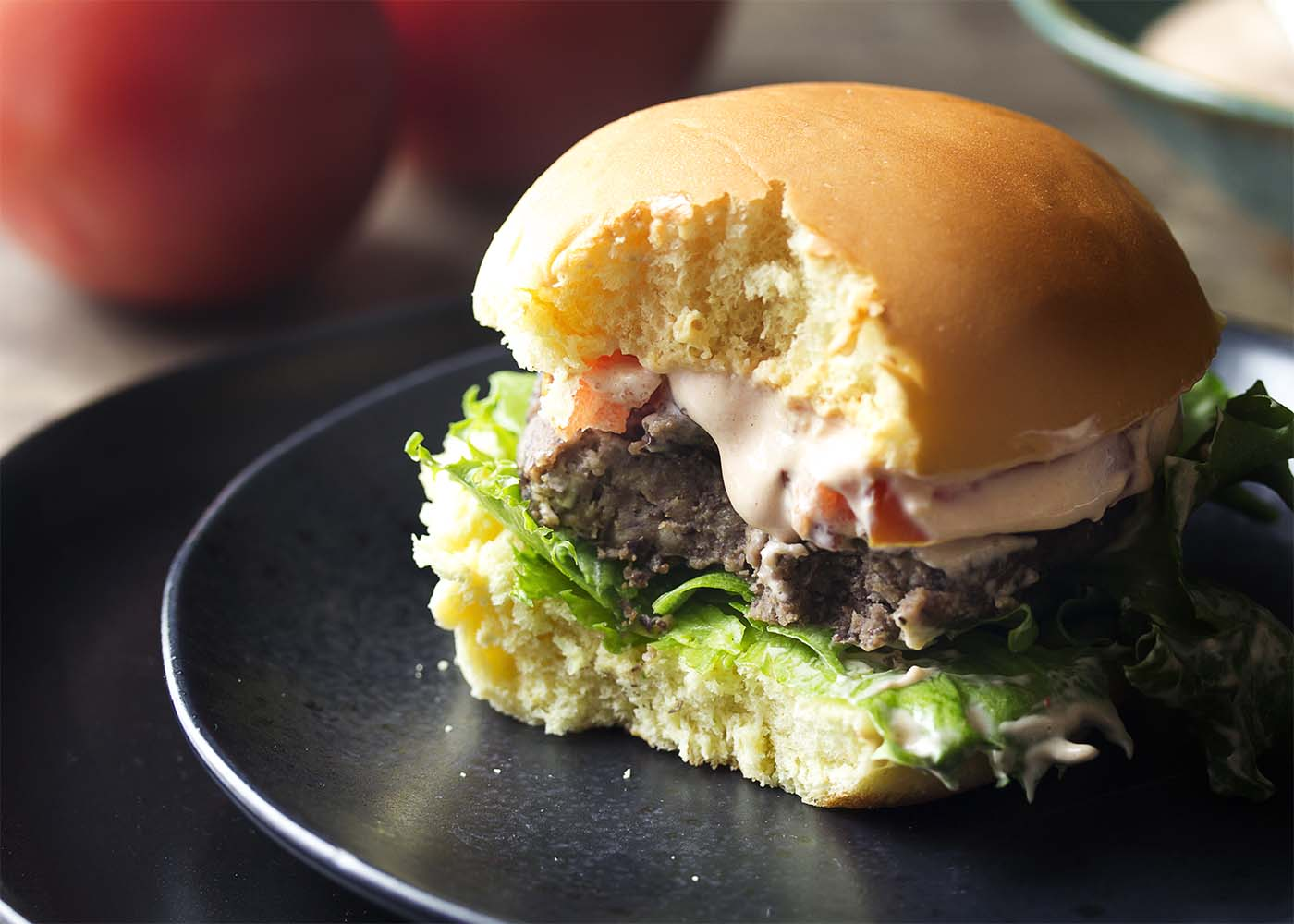Burger prepared with toppings and a bite taken out of it on a black plate.