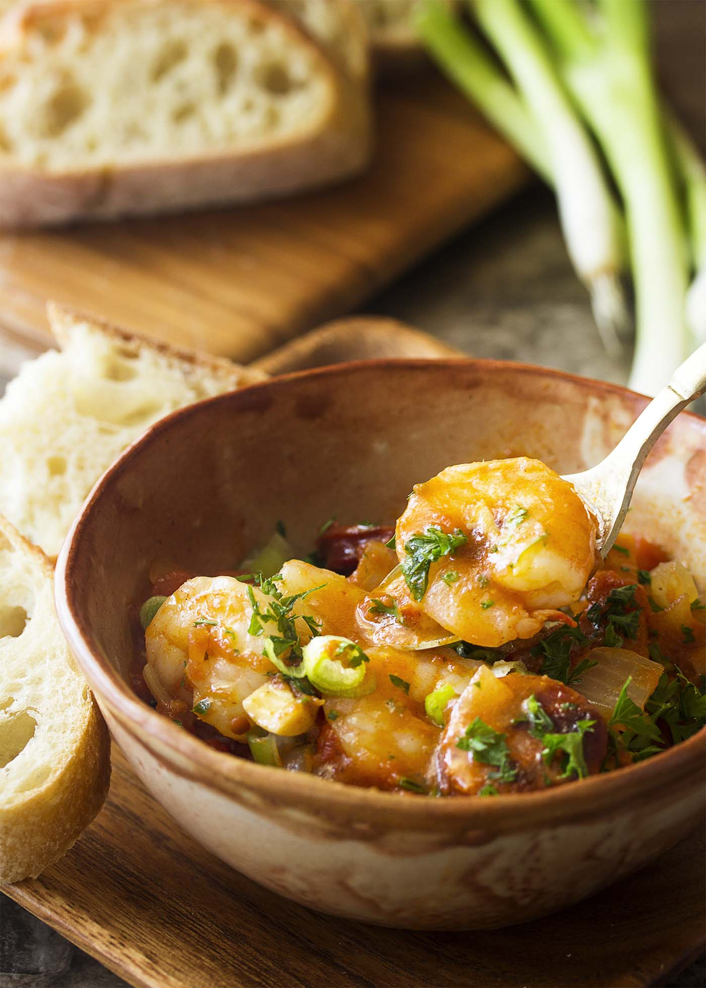A spoon holding up a shrimp from a bowl of shrimp and chorizo stew.