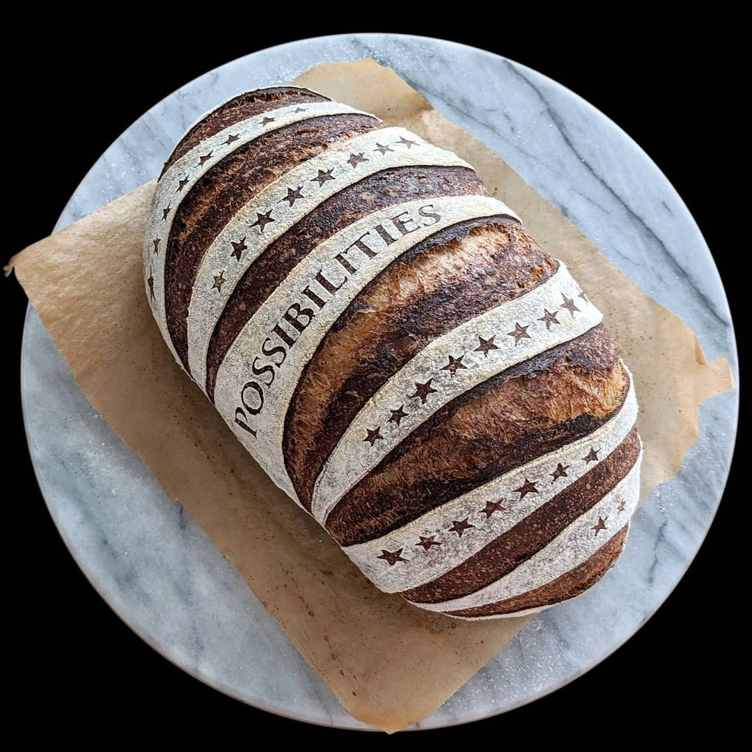 Beautiful sourdough bread with a star design and the word possibilities on it.