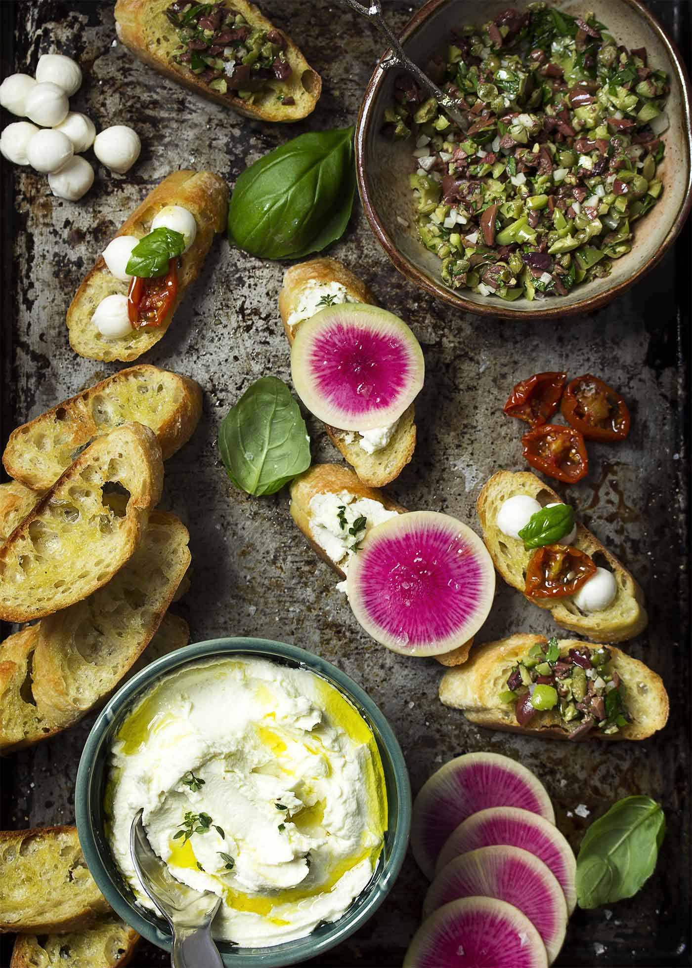 Top view of a tray of crostini, topped and plain along with bowls of spreads.