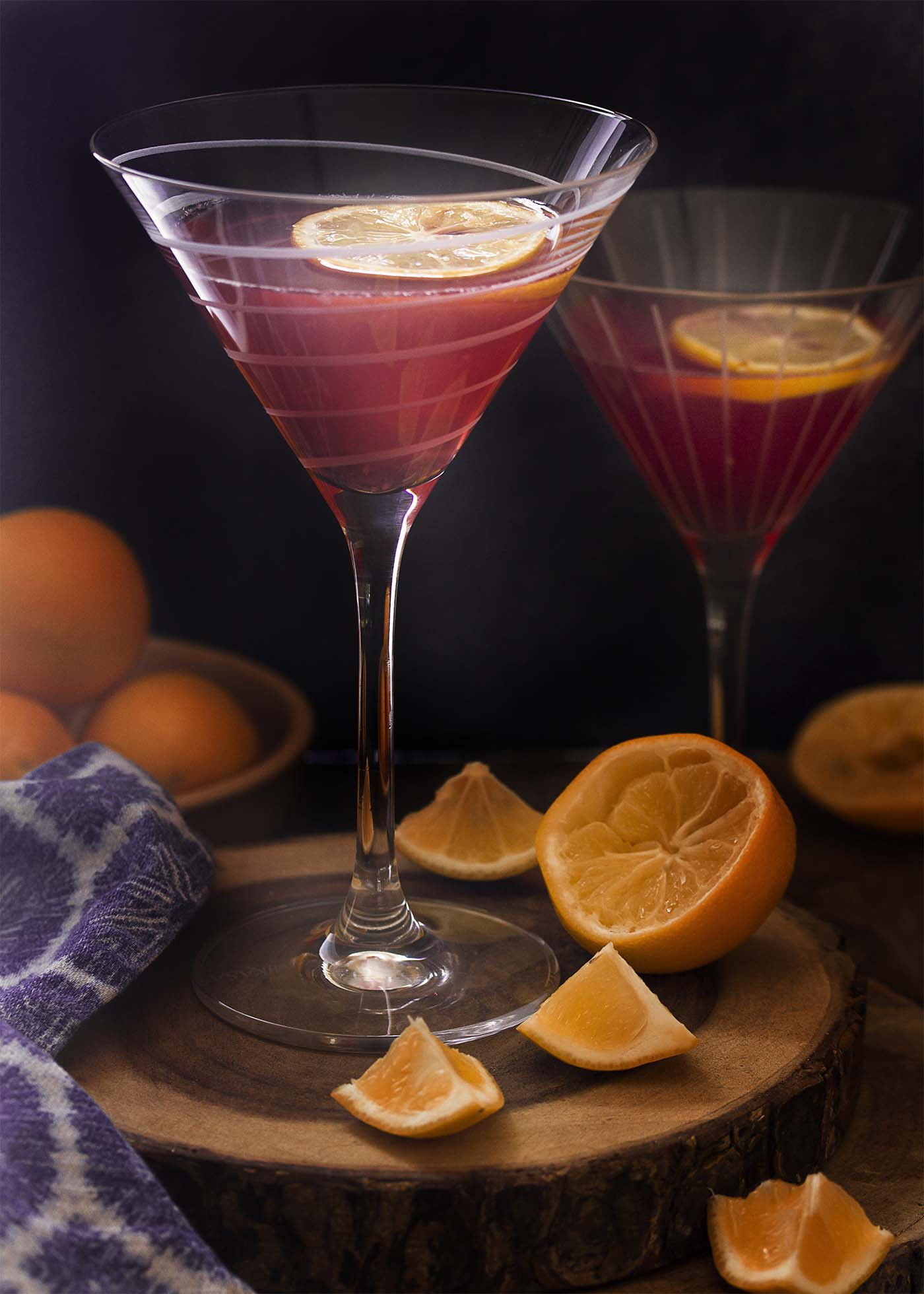 Two tall martini glasses filled with meyer lemon cosmos each garnished with a lemon slice.