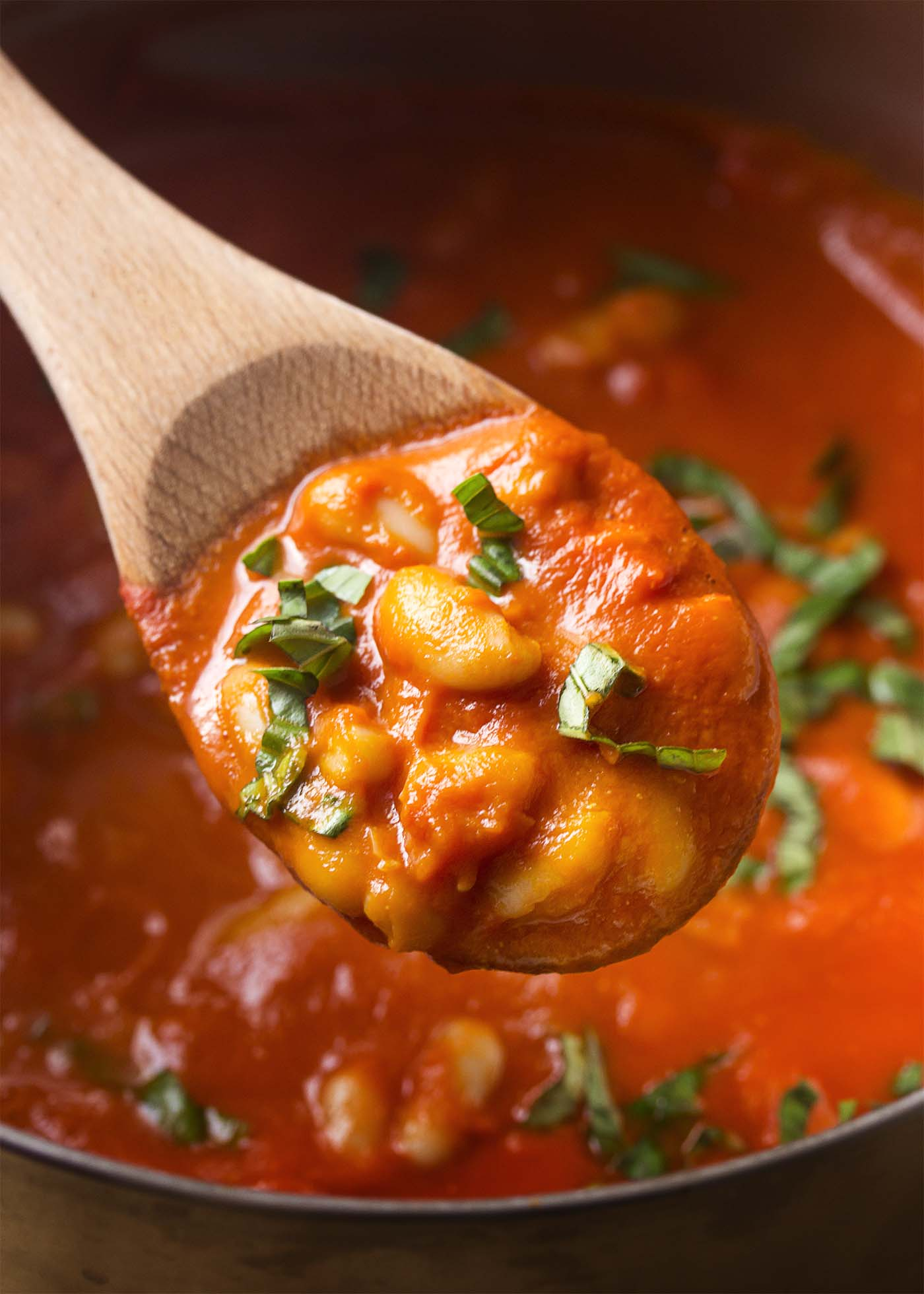A wooden spoon lifting a spoonful of beans and sauce out of a pot.