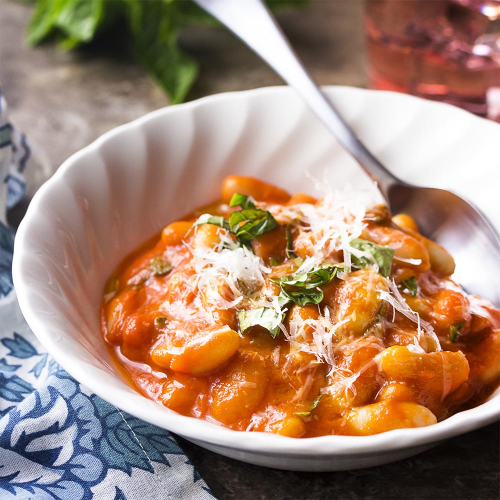 A white bowl of beans in pomodoro sauce topped by cheese and herbs.
