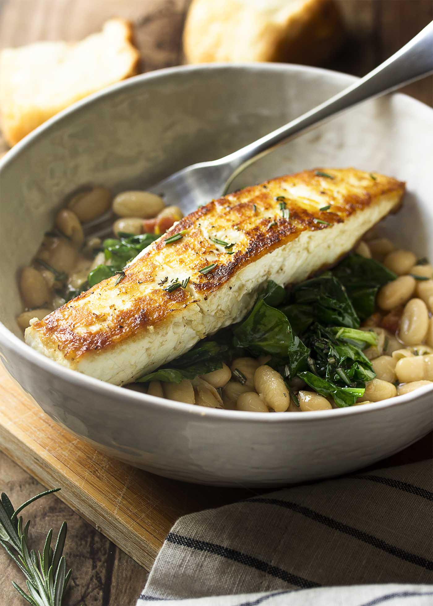 Large dinner bowl of white beans topped by sauteed spinach and a piece of golden brown fish.