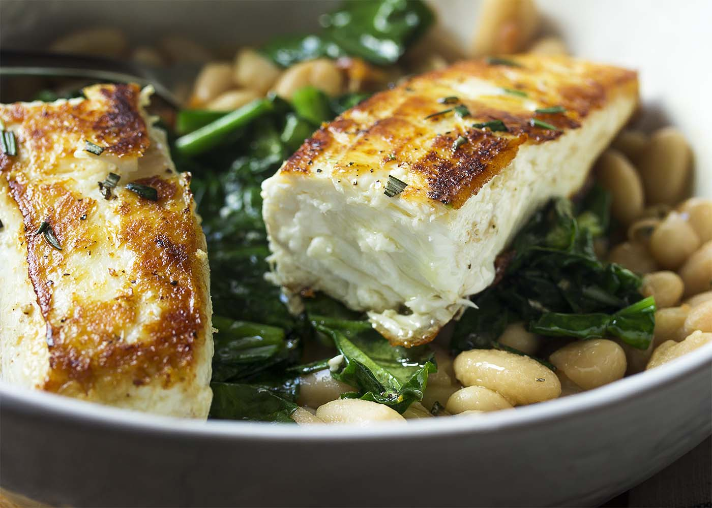 Close up of a piece of halibut showing the seared outside and juicy inside.