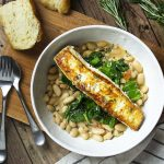 Have dinner in a bowl with pan seared halibut over creamy white beans and sauteed spinach! You'll love that this Mediterranean recipe is healthy, delicious, and quick.   justalittlebitofbacon.com #mediterraneanrecipes #halibut #fishrecipes #dinnerrecipes #easydinner