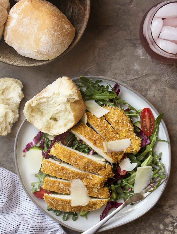 Baked parmesan chicken is an easy meal idea! These cutlets are pounded thin, then breaded in browned bread crumbs to make a crispy, oven baked meal perfect over a salad for a light dinner. | justalittlebitofbacon.com #chickenrecipes #dinnerrecipes #chicken #chickenbreast