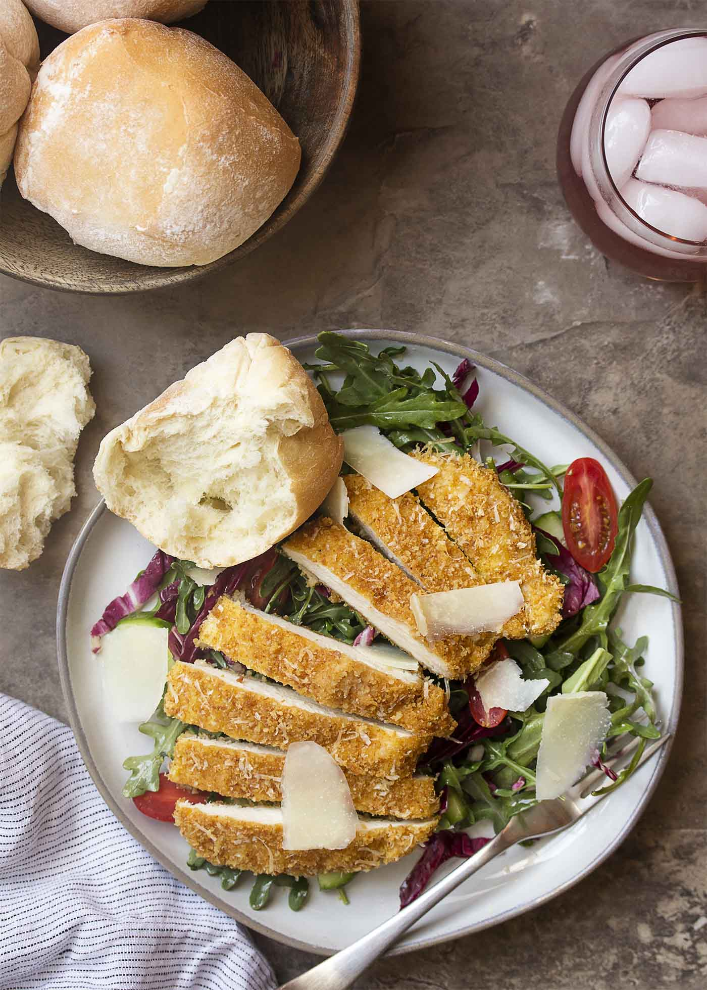 Top view of a plate of salad topped with slices of crispy parmesan baked chicken breast.