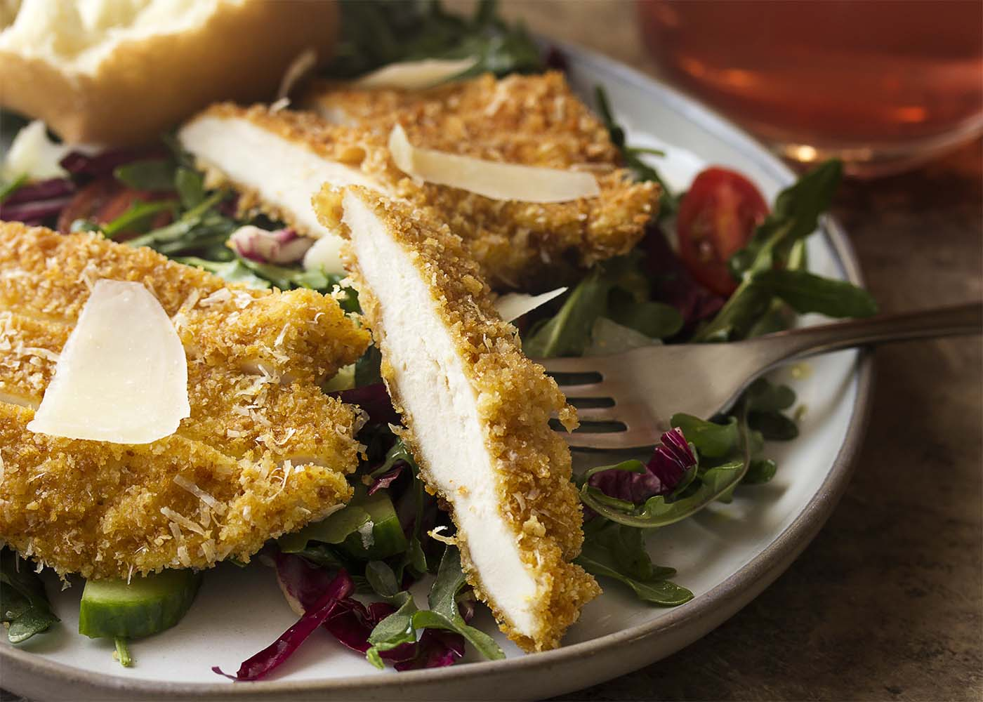 Close up of a slice of crispy breaded chicken breast on a plate with salad.